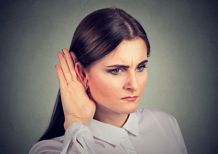 Young preoccupied girl having problems with hearing while listening to gossip.  Stock Photo