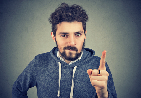 Hipster man showing his dislike and pointing with finger accusingly.
