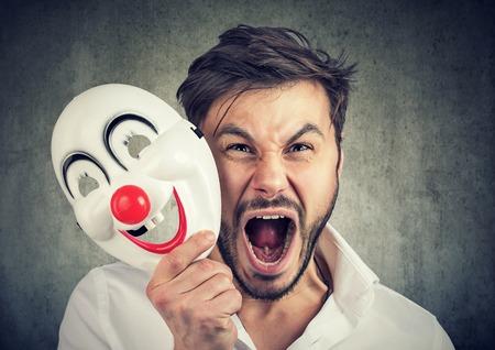 Retrato joven enojado gritando hombre quitándose una máscara de payaso aislada sobre fondo de pared gris. Emociones humanas sentimientos
