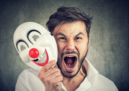 Portrait young angry screaming man taking off a clown mask isolated on gray wall background. Human emotions feelings Foto de archivo