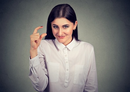 Young laughing woman showing little size with fingers looking at camera.