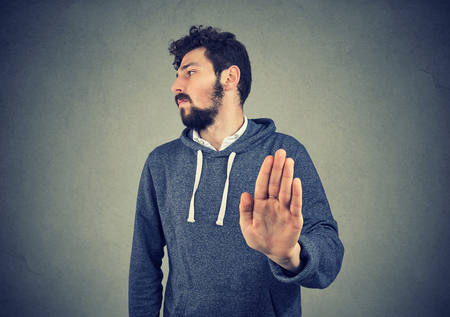 Annoyed angry man with bad attitude giving talk to hand gesture isolated on gray background. Negative emotion face expression feeling body language Stok Fotoğraf