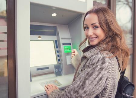 Młoda szczęśliwa kobieta z kartą kredytową za pomocą bankomatu