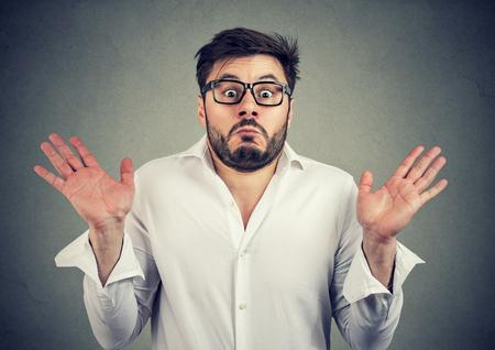 Jeune bel homme dans des lunettes regardant inquiet confus et haussant les épaules avec les épaules en regardant la caméra Banque d'images - 98035639