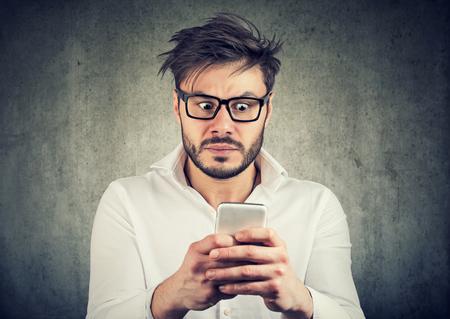 Junger bärtiger Mann in Gläsern smarpthone aufpassend und mit schlechten Nachrichten erschrocken schauend. Standard-Bild
