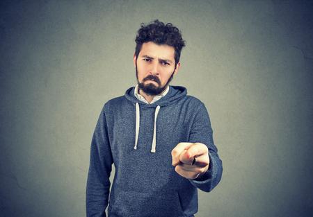 Young sad man with beard pointing at camera indicating guilt and blaming in anger.