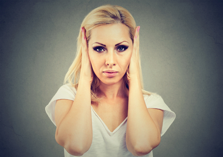 Young serious woman covering ears from rumors and noise avoiding problems and looking annoyed.  Stock Photo