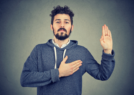 Sincere young man swearing with hand on heart