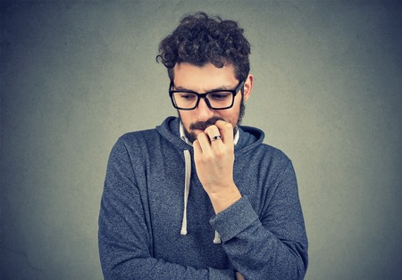 Closeup portrait nervous man biting fingernails craving something and anxious on gray wall background. Negative human emotion facial expression perception