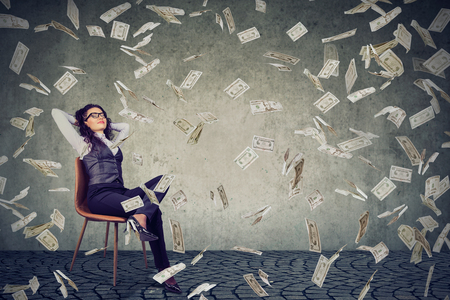 Young content woman sitting on chair in rain of flying bills happy with financial independence. Stock Photo
