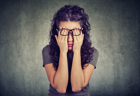 Closeup portrait young woman in glasses covering face eyes with both hands isolated on gray wall background