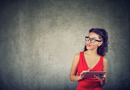 Elegant young businesswoman in red dress using tablet leaning to wall, looking up and planning