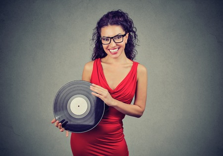 Joyful beautiful young woman showing a vintage vinyl