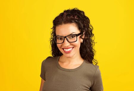 Cheerful content brunette in glasses smiling happily at camera on yellow background.