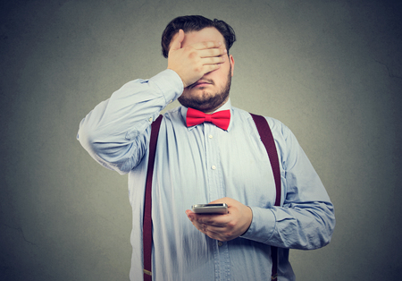 Sad regretful young man with mobile phone covering with hand his face  Stock Photo