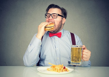 Business man eating junk food drinking beer Banque d'images