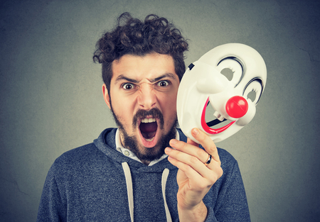 Portrait young upset angry screaming man holding a clown mask isolated on gray wall background. Human emotions feelings