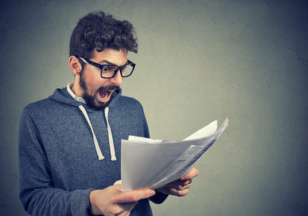 Angry stressed screaming man looking at documents papers isolated on gray wall background. Negative emotions face expression  Stock Photo