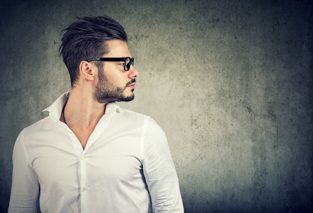 Stylish bearded guy with trendy hairstyle wearing glasses and white shirt standing in profile on gray background.