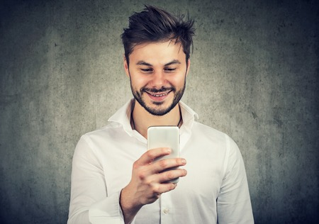 Content bearded man in white shirt exploring new smartphone happy with upgrade.