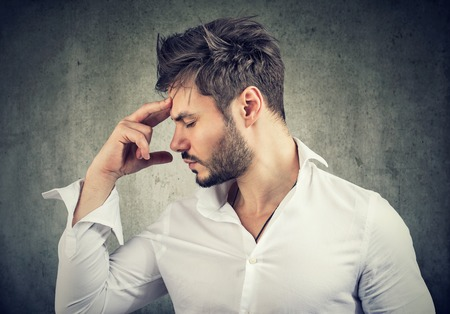 Formal man touching forehead thinking deeply and looking for solution.