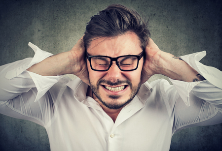 Frowning bearded man in glasses covering ears having hysteria and stress.  Stock Photo