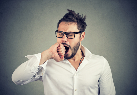 Young man in white shirt and glasses looking sleepy after long working day and yawning on gray background.  Stock Photo