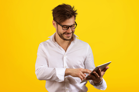 Smiling man in shirt and eyeglasses surfing new tablet happy with upgrade on yellow background.