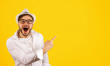 Cheerful hipster guy in white shirt and hat pointing up showing advertisement on yellow background.
