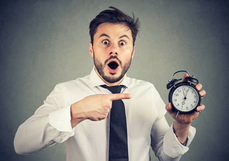 Expressive man in formal outfit holding alarm clock and pointing at it in surprise being busy.  Stock Photo