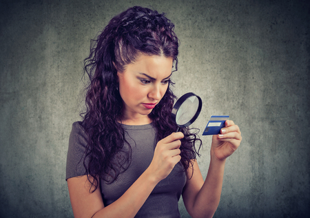 Curious woman looking at credit card through magnifying glass isolated on gray background