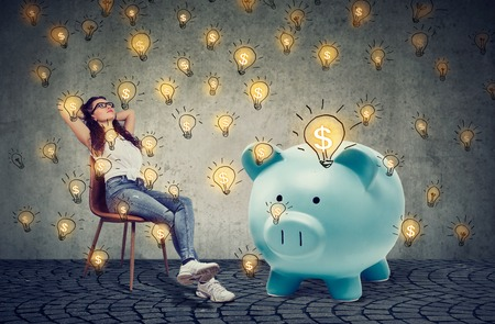 young casual businesswoman with big piggy bank relaxing sitting on chair generating bsuiness ideas  Stock Photo