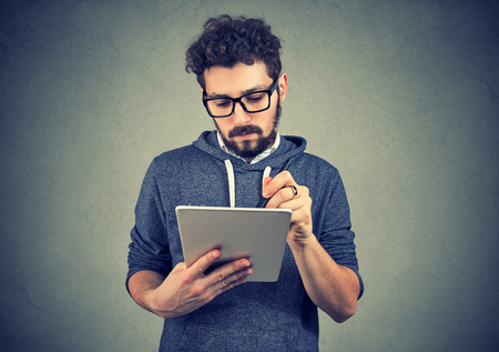 Serious hipster man with tablet computer and pen has an idea, brainstorming new plan looking at screen Stock Photo