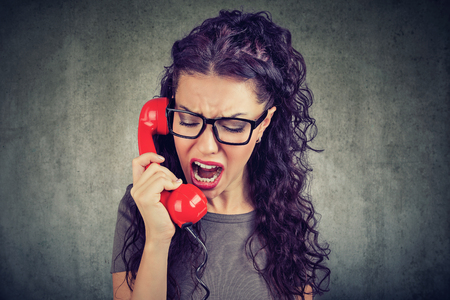 Young angry woman yelling on the phone