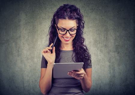 Happy woman with tablet computer and pen has an idea, brainstorming new plan looking at screen