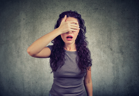 Regretful young woman covering her eyes Stock Photo