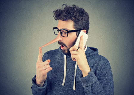 Surprised young man with long nose talking on mobile phone isolated on wall background. Liar concept. Human emotion feelings character traits Stock Photo