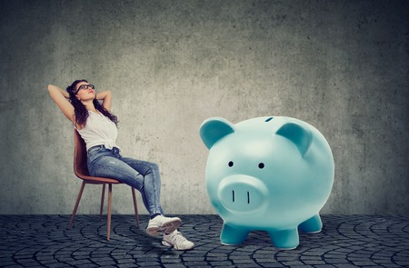 young casual woman with big piggy bank relaxing sitting on chair