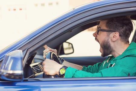 Driver di uomo hipster arrabbiato di profilo laterale. Le emozioni umane negative affrontano l'espressione Archivio Fotografico