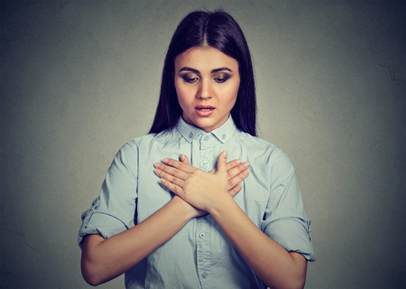 Young woman with asthma attack or respiratory problem isolated on gray background Standard-Bild