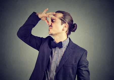 Disgusted man pinches nose with fingers looks with disgust something stinks bad smell isolated on wall background. Human face expression reaction