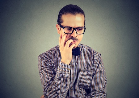 Closeup portrait nervous business man biting fingernails craving something and anxious on wall background. Negative emotion facial expression perception