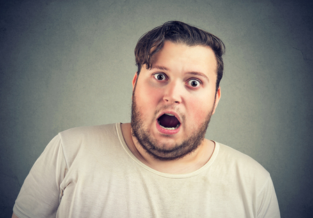 Closeup of overweight man looking scared with mouth opened at camera on gray background.  Stock Photo