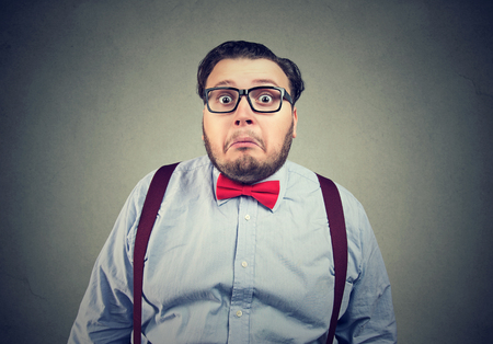 Funny obese man in bow tie and glasses looking awkward and perplexed on gray background.