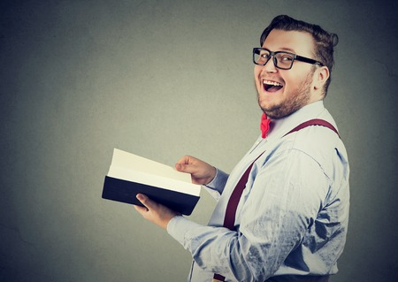 Side view of happy chubby man reading interesting book and laughing at camera on gray background