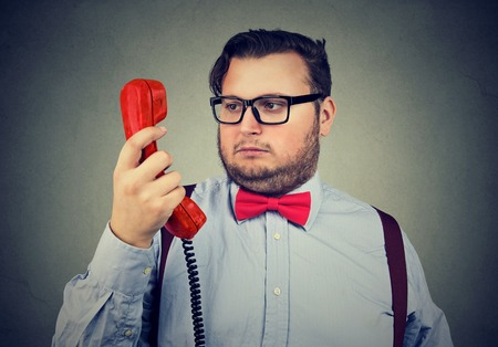 Formal chubby man in bow tie and glasses looking at handset in doubt and misunderstanding on gray