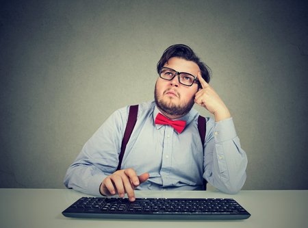 Overweight man in formal outfit sitting at computer trying to remember password and thinking with concentration Stockfoto