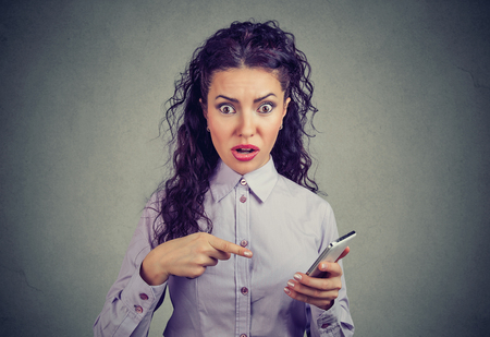 Shocked girl in shirt holding smartphone and pointing at it sunned with bad breaking news