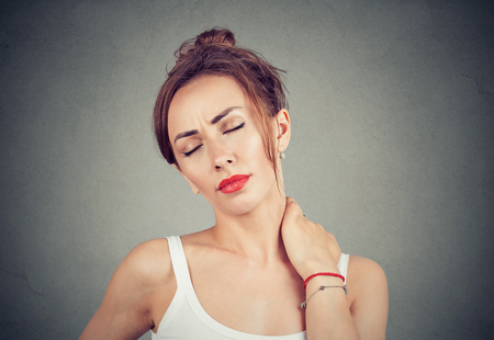 Pretty brunette woman rubbing neck having problems with spine and looking overworked on gray background