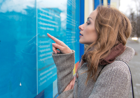 Side view of woman in coat outside exploring information board on street reading news and searching job